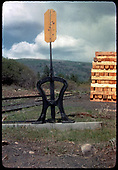 Harp switchstand along Grady siding with stack of new railroad ties in background.  This is a Mike Blazek Type D with a yellow target that was generally used for derails.<br /> RGS  Grady, CO  Taken by Kindig, Richard H. - 6/4/1951