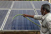 An employee cleans solar panels at the Safe Water Network iJal station in Rangsaipet, in Waragal, Telangana, Indiia, on Saturday, February 9, 2019. Photographer: Suzanne Lee for Safe Water Network
