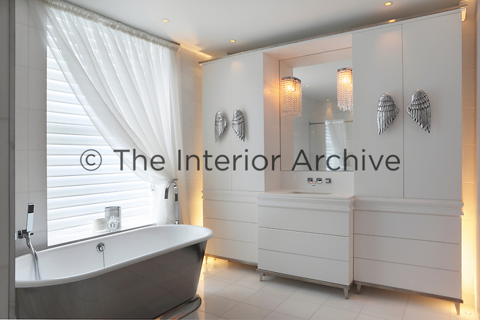 A luxurious bathroom furnished with a silver roll top bath and a washstand unit of cupboards and drawers for storing bits and bobs away from sight