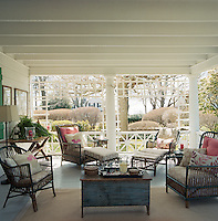 A rustic wooden table surrounded by wicker chairs in the breezy covered side porch.