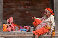 Pashupatinath, Nepal.  Female Sadhu, a Hindu Ascetic, or Holy Woman, Rests in a Pati, an Open-air, Covered Resting Place.