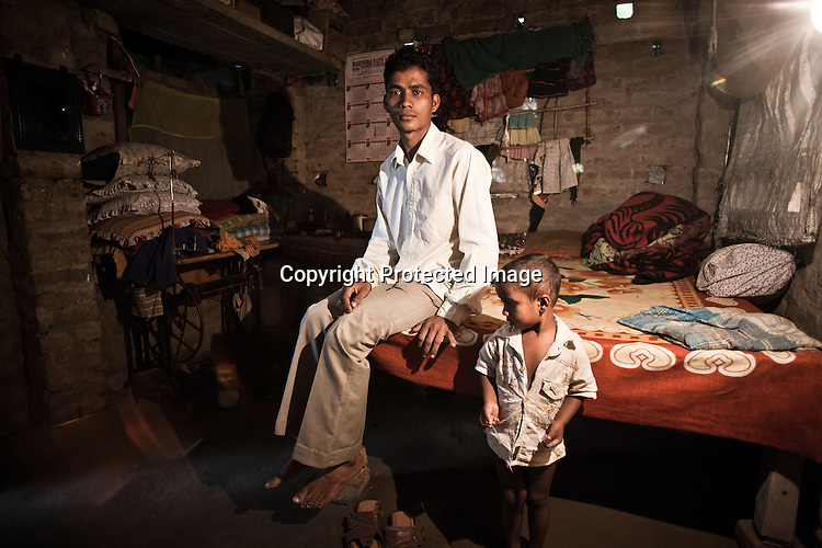 21 year old Rafik Gazi, from the Chowduli class is seen with his 3 year old son, Rakibul Gazi in his family house in Chaymalpur village of North 24 Parganas in West Bengal, India. Photo: Sanjit Das/Panos for The Wall Street Journal. Slug: ICASTE