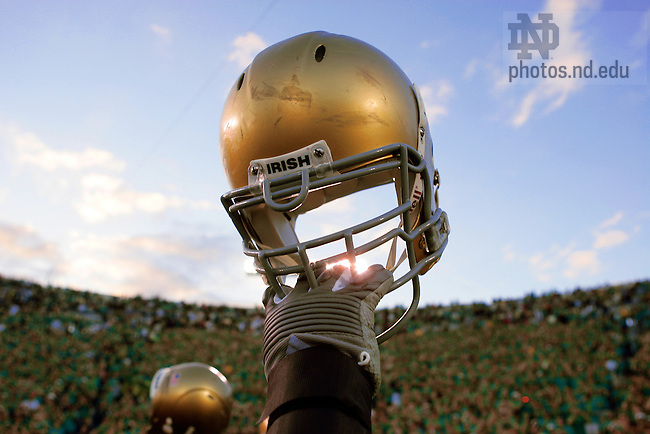 Notre Dame football players hold up their helmets in the the traditional post-game salute to the Notre Dame Stadium student section.<br /> <br /> Photo by Matt Cashore