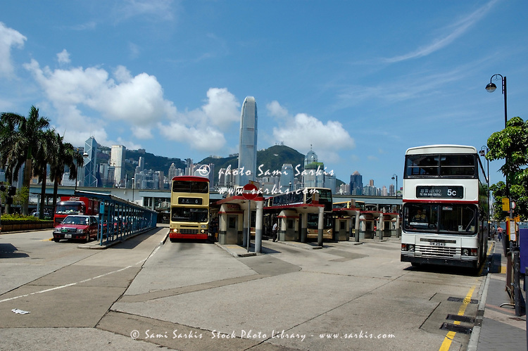 Bus station and ferry dock with harbor and skyscrapers in the background, Kowloon, Hong Kong, China.