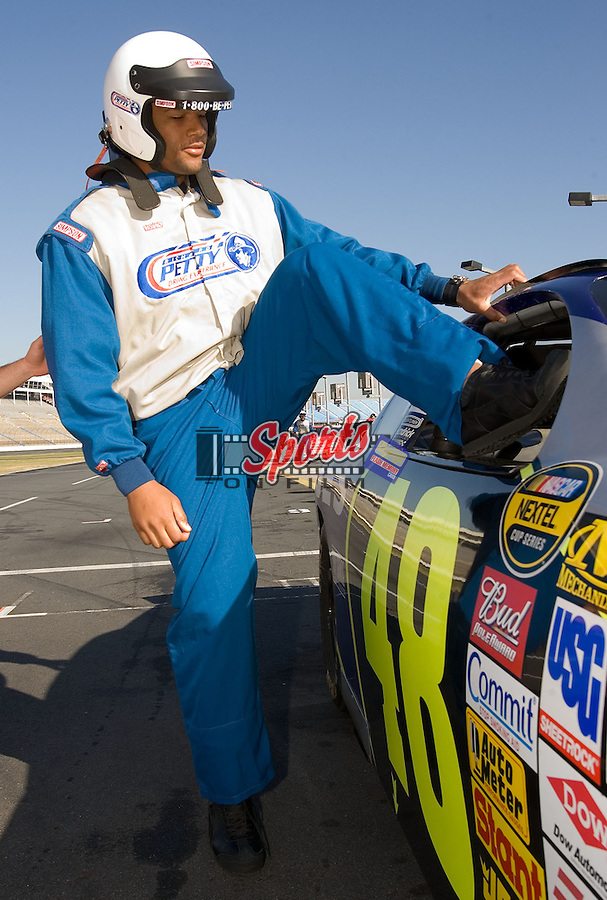 """At 6' 5"""" tall, Wake Forest Demon Deacon defensive end Jeremy Thompson is a tight fit as he climbs into a race car at the Richard Petty Driving Experience at Lowe's Motor Speedway Thursday, December 27, 2007 in Concord, NC."""