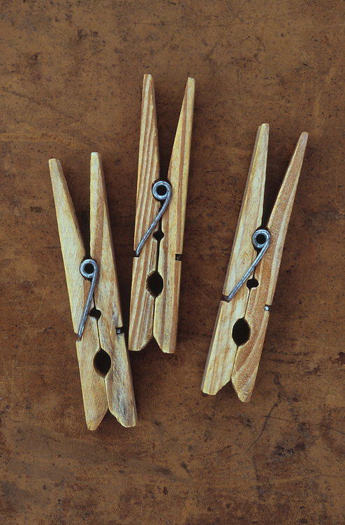 Three vintage used spring-loaded wooden clothes pegs lying on scuffed brown leather