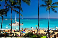 A beatiful view of Waikiki Beach with its palm trees, white sands and catamarans. This view is from the Outrigger Waikiki On The Beach Hotel.