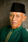 An Indonesian man in a green jacket and a black hat, Lombok, Indonesia.