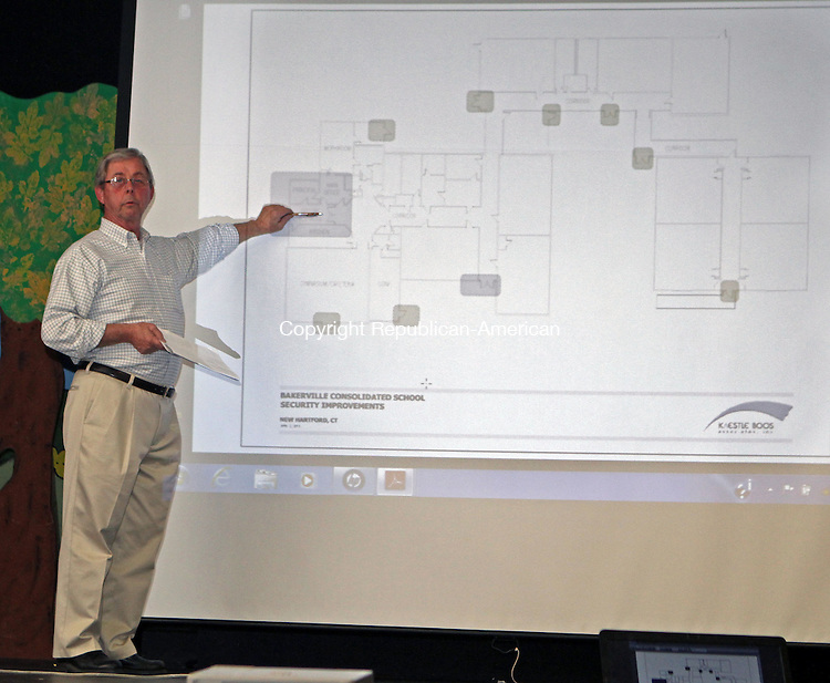 New Hartford, CT-041113MK03 Roy Litchfield, building oversight committee member and a co-chair on the the school building study committee, describes details of a projected image on the proposed security upgrade expenditures to the town's three schools during a Board of Finance hearing Thursday evening at the Ann Antolini School in New Hartford.  About thirty five attendees came to listen and comment on the proposal. Michael Kabelka / Republican-American..