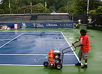 Tournament workers dry the courts following a thunderstorm during the Legg Mason Tennis Classic at the William H.G. FitzGerald Tennis Center in Washington, DC.
