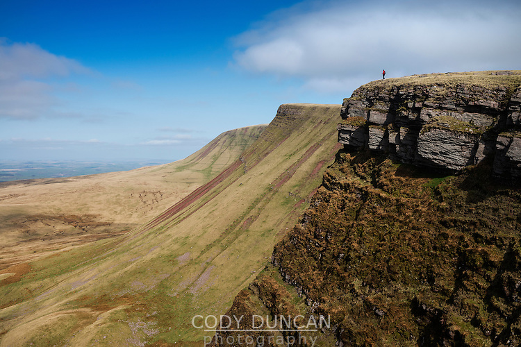 Female hiker on Carmarthen Fans - Bannau Sir Gaer with Picws Du in distance, Black Mountain, Brecon Beacons national park, Wales