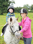 Catriona Halpenny helps JJ Corrigan with her pony ride as part of the Turfman Festival in Ardee. Photo: Colin Bell/pressphotos.ie