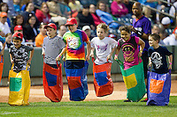 Young fans compete in a sack race between innings of the Carolina League game between the Carolina Mudcats and the Winston-Salem Dash at BB&T Ballpark on April 13, 2013 in Winston-Salem, North Carolina.  The Dash defeated the Mudcats 4-1.  (Brian Westerholt/Four Seam Images)