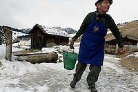 "Lorenzo Miriboch carries water from the cattle trough because his pipes are frozen in La Valle. Lorenzo Miriboch lives alone in the Cianz district of the town.<br /> <br />  We knocked on his door and window for 20 minutes and finally a hand came across the curtain and a voice came out saying ""nobody home.""  We then got a neighbor to bring him out and by the end of our stay he was kissing Melissa and wanting to bring us more Schnopps."