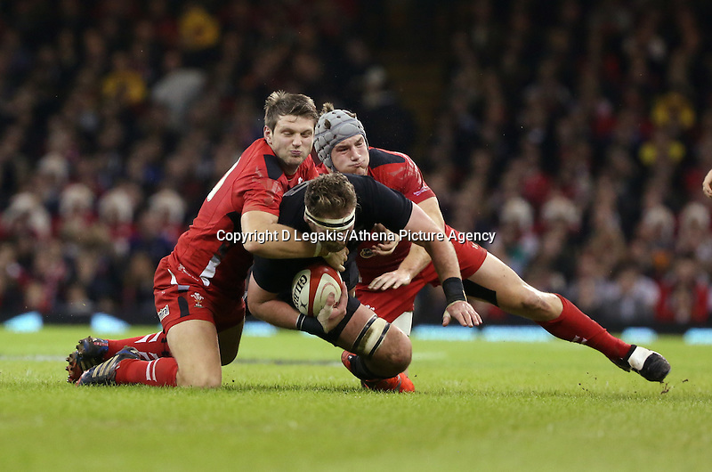 Pictured: Kieran Read of New Zealand (C) is brought down by Dan Biggar (L) and Jonathan Davies (R) of Wales Saturday 22 November 2014<br /> Re: Dove Men Series 2014 rugby, Wales v New Zealand at the Millennium Stadium, Cardiff, south Wales, UK.