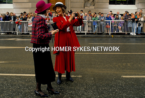 'CITY OF LONDON', TWO WOMEN CHATTING AND LAUGHING WHILST TAKING PHOTOGRAPHS OF THE LORD MAYORS SHOW, 1990