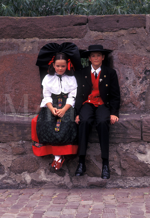 France, Alsace, Kaysersberg, Haut-Rhin, Europe, wine region, Girl and boy dressed authentic costumes sit on a stone wall in the village of Kaysersberg in the wine region of Alsace.
