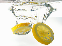 Lemon slices splashing underwater, white background, studio