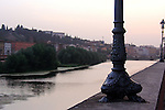 A bronze lamposts adorn the sidewalks of  the  river Arno in Florence Italy.