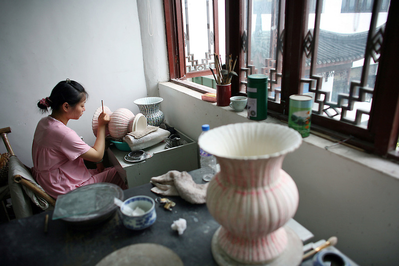 A artisan decorates a vase in a the Jiayang factory, a Jingdezhen porcelain factory, June 26, 2006.