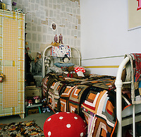 A child's bedroom with a white painted cast-iron bed draped with a patchwork cover. A small painted wardrobe stands against one wall.