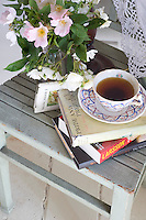 A posy of wild dog roses has been placed next to a cup of tea and a stack of books on a kitchen chair used as a bedside table