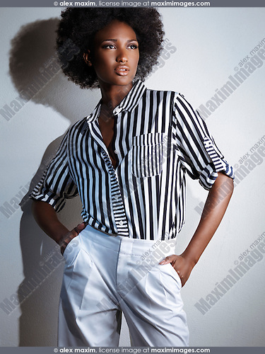 Beautiful young african american black woman wearing white pants and a stripy shirt. Artistic fashion photo.