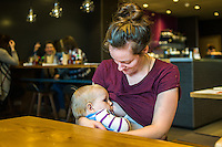 A mother breastfeeding her 10 month old son in a restaurant.<br /> <br /> Herefordshire, England, UK<br /> 09/01/2015<br /> <br /> © Paul Carter / wdiip.co.uk