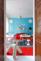 "In the sitting room the floor has been painted scarlet red and the panelled walls a bright turquoise and the room is furnished with a mixture of colourful contemporary pieces including a chair in the shape of a dog, called ""Puppy"""