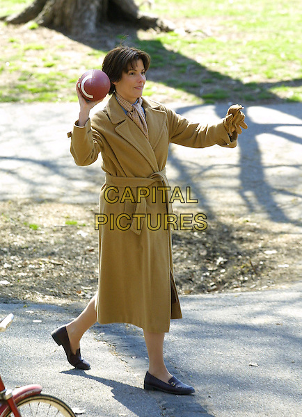 "SANDRA BULLOCK.On the film set of her new movie ""Every Word I Say Is True"" in Fort Greene Park, Brooklyn, New York. .April 12th, 2005.full length bag park brown beige trench coat throwing american football ball playing sport gesture .www.capitalpictures.com.sales@capitalpictures.com.©Capital Pictures"