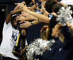 Kemba Walker high fives people holding the NCAA trophy as he enters Gampel for the victory rally, Tuesday, April 5, 2011. (Jim Michaud/Journal Inquirer)