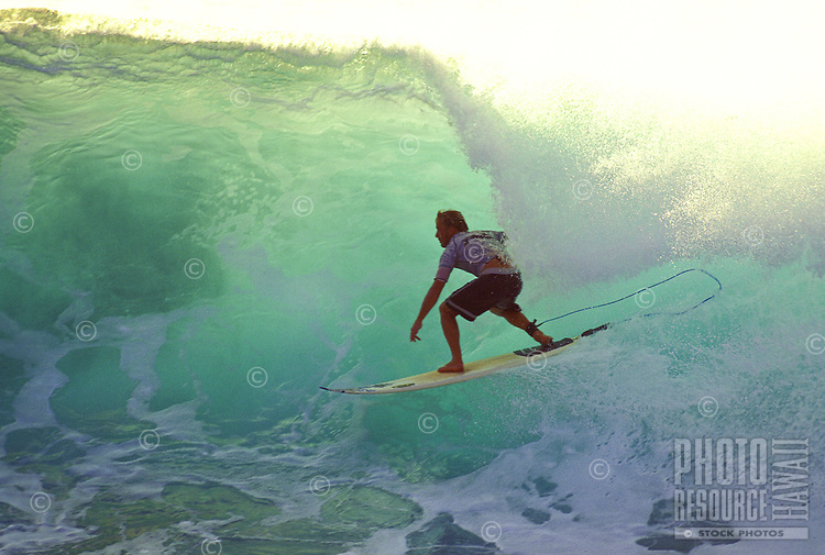 A surfer rides a translucent tube of water formed by a huge wave off the island of Maui.