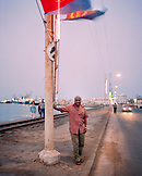 ERITREA, Massawa, portrait of a man standing under Eritrean flags with the Port of Massawa in the distance, the Red Sea