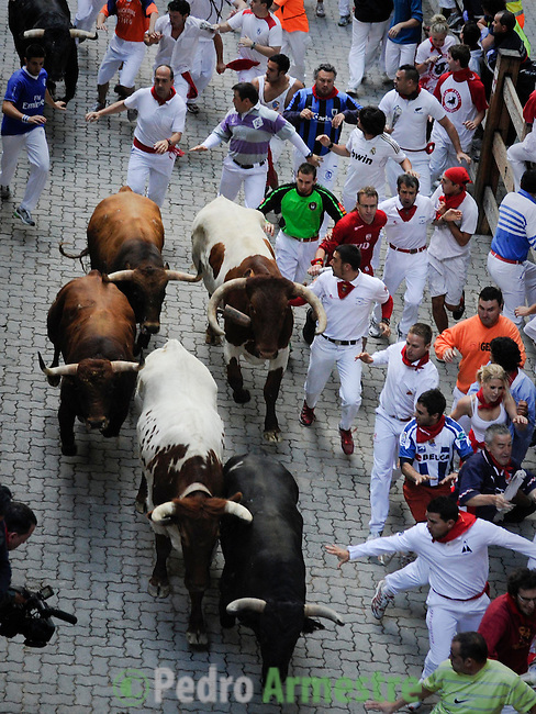 Participants run in front of Victorinano del Rio Cortes's bulls during the sixth San Fermin Festival bull run, on July 12, 2012, in Pamplona, northern Spain. The festival is a symbol of Spanish culture that attracts thousands of tourists to watch the bull runs despite heavy condemnation from animal rights groups . (c) Pedro ARMESTRE