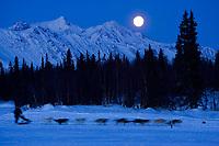 Aaron Burmeister streaks along the lake as a near-full moon sets over the Alaska Range at Finger Lake checkpoint