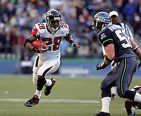 Atlanta's Warrick Dunn (28) runs the ball as Seahawks Isaiah Kacyvenski (58) closes in to make the tackle .Atlanta Falcons vs. Seattle Seahawks at Qwest Field in Seattle on Sunday Jan. 2, 2005 Photo by Kevin P. Casey/WireImage.com