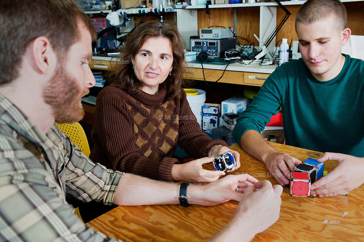 Daniela Rus (center) is a Professor of Electrical Engineering and Computer Science and Director of the Computer Science and Artificial Intelligence Laboratory at MIT in Cambridge, Massachusetts, USA. Working postdoctoral associate Kyle Gilpin (plaid) and robotics engineer John Romanishin (green), her lab, the Distributed Robotics Lab, has developed M-Blocks, 50mm cube robots that can reconfigure themselves into various arrangments using self-propulsion and magnets.
