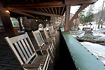 NEW PALTZ - MARCH 13: Rocking Chairs on Lakeside Balcony of historic Mohonk Mountain House. Wide angle horizontal view, with glimpse of frozen lake, distant small gazebo on one side and stone arched walkways and green and stone exterior of the inn on other side, on winter morning of March 13, 2010, at New Paltz, New York, USA. For Editorial Use Only