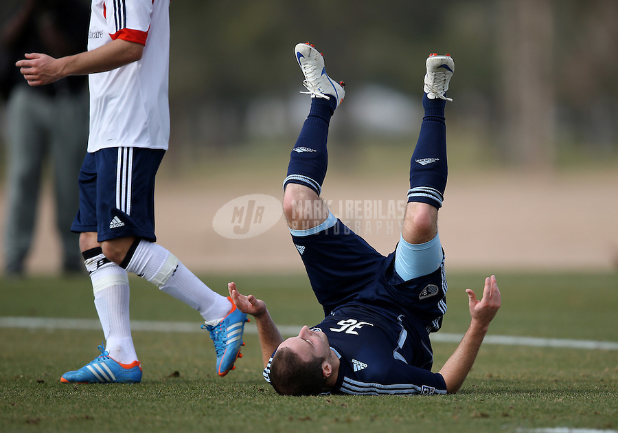 Jan. 25, 2013; Casa Grande, AZ, USA: Sporting KC midfielder Mike Reidy is upended against the New England Revolution during a preseason game at Grande Sports World. Mandatory Credit: Mark J. Rebilas-USA TODAY Sports