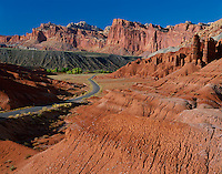 Capitol Reef National Park, UT: View of eroded badlands along the Scenic Drive with the Fremont River Valley and red cliffs of Capitol Reef in the distance