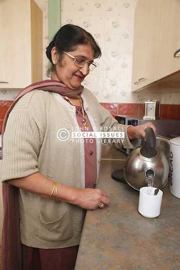 Elderly south Asian woman in kitchen pouring kettle.