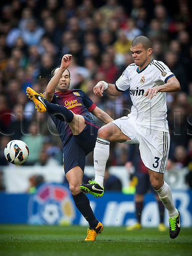 02.03.203 Madrid, Spain. Midfielder  Iniesta of FC Barcelona  (L) clears the ball away challenged by Defender Pepe of Real Madrid during the Spanish La Liga game between Real Madrid and Barcelona from the Santiago Bernabeu.