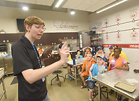 NWA Democrat-Gazette/FLIP PUTTHOFF <br /> STAINED GLASS ARTISTS<br /> Conner Newsom Doyle (cq) with The Scott Family Amazeum tells youngsters Tuesday June 25 2019 at the Boxopolis 2.0 camp how chocolate is made. Campers do architecture and design projects at the Amazeum during the camp that runs through June 28. They made stained glass windows out of candy pieces on Tuesday. The Amazeum and the Fay Jones School of Architecture and Design at the University of Arkansas teamed up to host the camp.