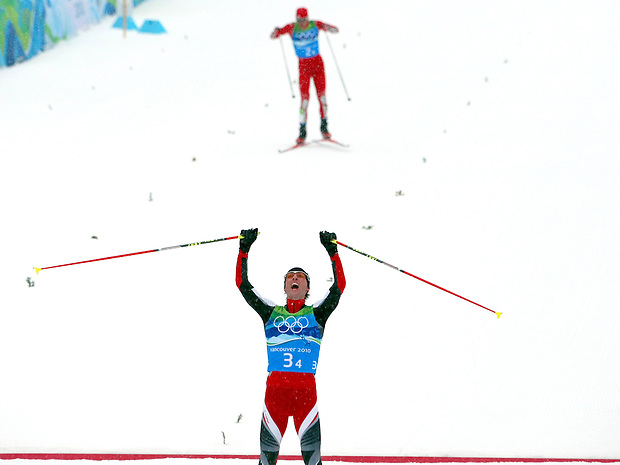 Austria's Mario Stecher claims the gold medal in front of USA's Bill Demong, at rear, who claimed silver for the U.S. in the men's nordic combined at the XXI Olympic Winter Games Tuesday, February 23, 2010 in Whistler, British Columbia.