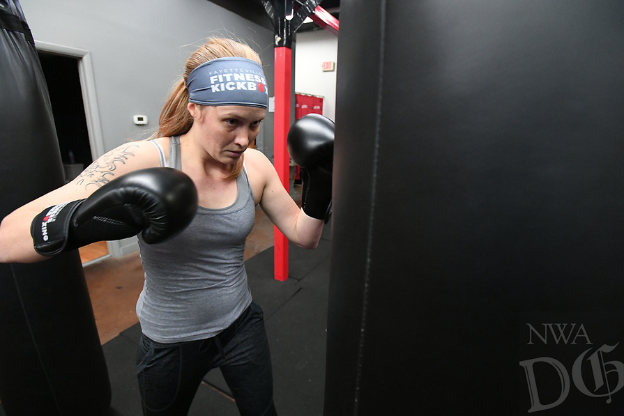 NWA Democrat-Gazette/J.T. WAMPLER Stephanie McGaugh of Goshen punches the bag during a kick-boxing class Wednersday Feb . 21, 2018 at Fayetteville Fitness Kickboxing.