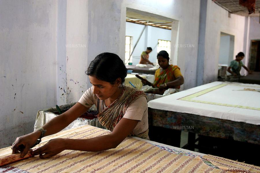 Bangladesh. Women tailor pieces of silk to make clothes. .Most of the silk produced by BRAC's beneficiaries is bought up by the Manikganj Foundation where the silk is dyed, and block printed and finally tailored into expensive kurtas and saris that are then sold through BRAC's sister-concern - the high-end designer store Aarong - which means bazaar. This is the final stage of a long process that began with the women who raise the silk-worms. ..Bangladesh. Des femmes taillent de large pièce de soie pour confectionner des vêtements..La plupart de la soie produite par les bénéficiaires du BRAC est acheté par la Fondation Manikganj où la soie est teinte, puis imprimée en block et finalement taillée en de chers kurtas et saris qui sont ensuite vendus par le reseau de vente du BRAC, le Aarong. C'est l'étape finale d'un long processus qui a commencé avec des femmes qui élevent des vers à soie.