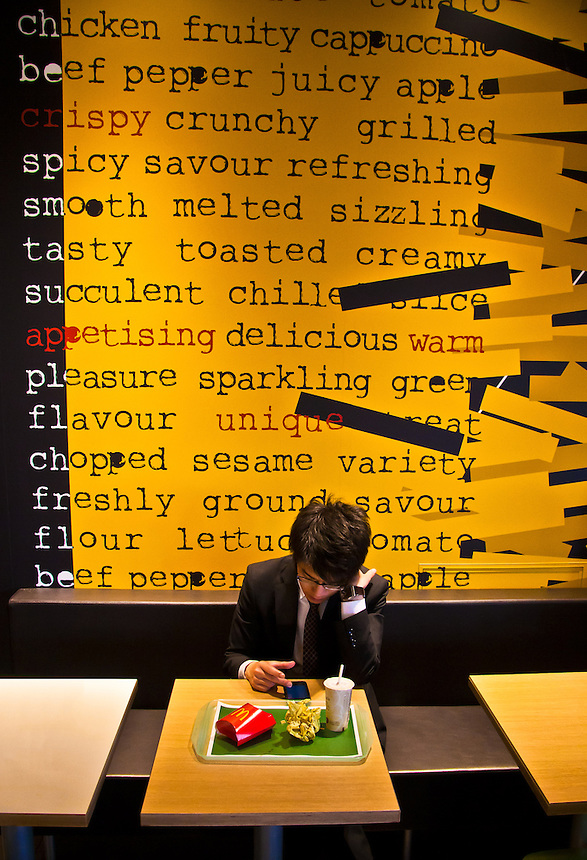 Saleryman digesting his McDonald`s lunch & latest news on his smart phone sitting in newly designed Tokyo restaurant.