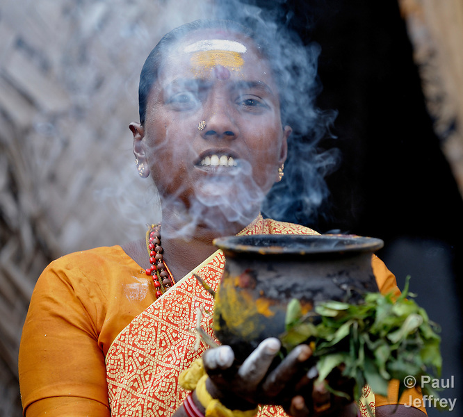 A woman uses incense to bless homes in the Dhobi neighborhood of Madurai, a city in the state of Tamil Nadu in southern India.