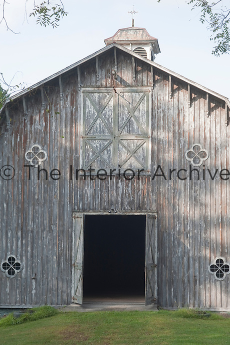 The clapboard wall of the double-height hayloft is punctuated with a series of flower-shaped windows