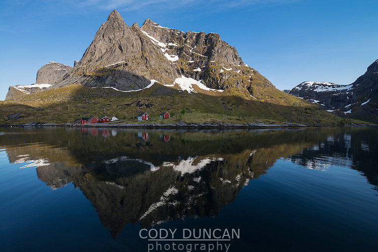 Tennestind mountain peak and coastal buildings reflect in Reinefjord, Moskenesøy, Lofoten Islands, Norway